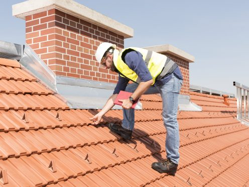 Product manager checking ventilation roof tiles in front of chimney standing on the roof wearing hard hat and safety jacket
