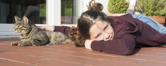 Girl with cat relaxing in the sun on the clay paved terrace